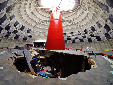 """National Corvette Museum Skydome Sinkhole: Pictured in the sinkhole: 1962 Black Corvette, 1993 40th Anniversary Ruby Red,the 2009 """"Blue Devil"""" ZR1 and 1 millionth Corvette (under '62)  Permission given to use this image with credit to the National Corvette Museum"""